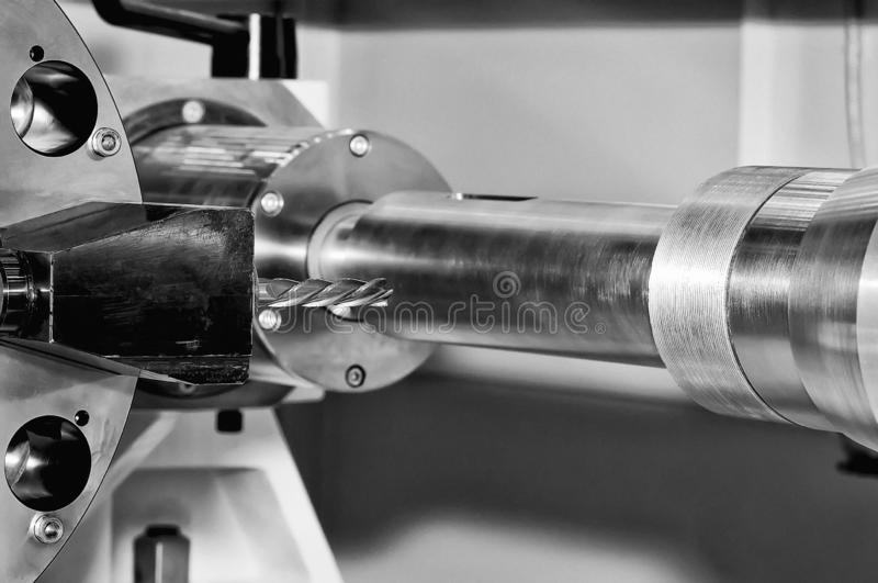 Metal billet on milling machine. Black and white toned. Metal billet is machined on an industrial milling machine. Black and white toned image. Close up stock photography