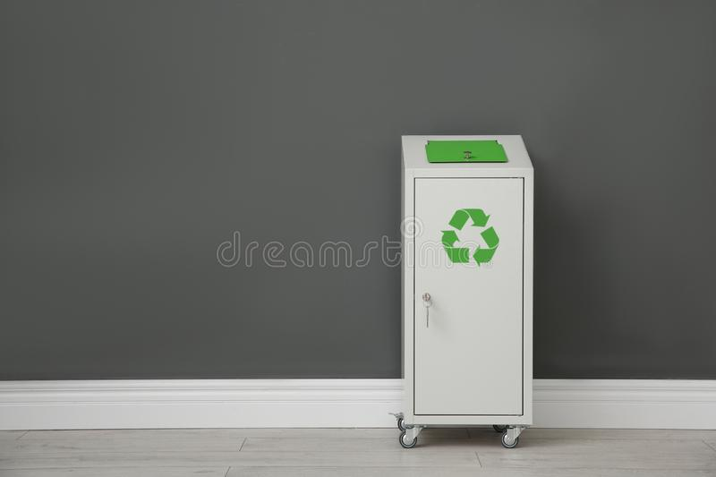 Metal bin near color wall, space for text. Waste recycling royalty free stock photo
