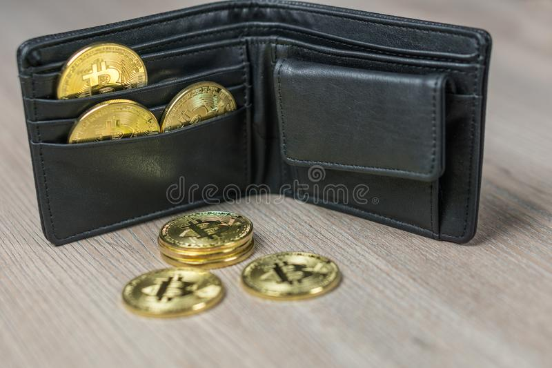 Metal bitcoins in black leather wallet. Bitcoin - modern virtual. Metal bitcoins in brown leather wallet. Bitcoin - modern virtual stock photo