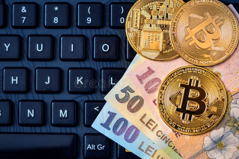 Metal Bitcoins and Romanian money Ron, New Lei over the keyboa stock photos