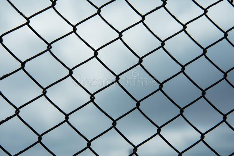 Metal black fence-mesh netting. Gloomy cloudy gray sky. stock photos