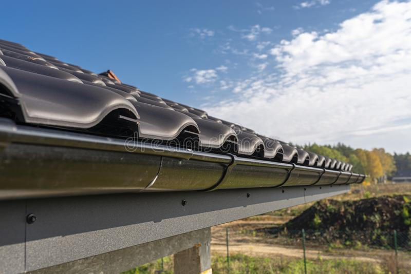 A metal, black gutter on a roof covered with ceramic tiles. Close up shot. A metal, black gutter on a roof covered with ceramic tiles. Close up shot stock images