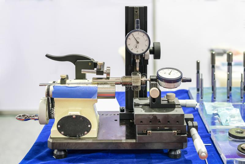 Metal bolt and nut with dial gauge during setup on modern thread checking instrument for industrial on blue table stock photos