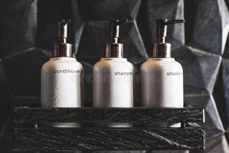 Metal bottles of shampoo, conditioner, shower gel. Three white metal bottles of shampoo, conditioner, shower gel on wooden shelf in modern hotel bathroom with stock photos