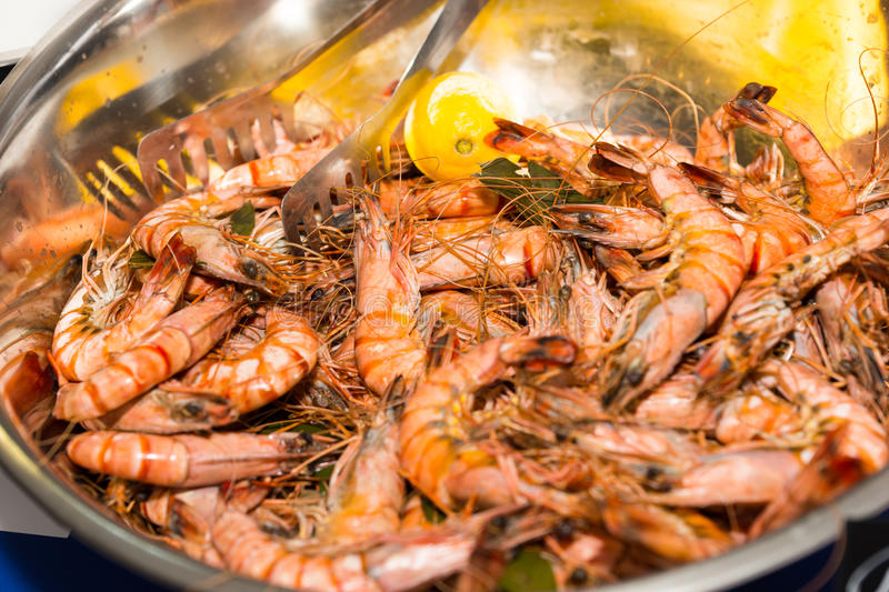 Metal Bowl Filled with Cooked Prawns and Lemon stock images