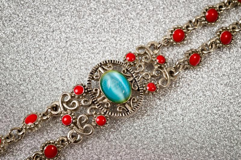 Metal bracelet on a female bracelet with emerald and red pebbles shot large on a silver background stock photos