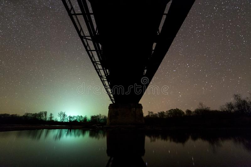 Metal bridge on concrete supports reflected in water on dark starry sky background, bottom view. Night photography concept royalty free stock photos
