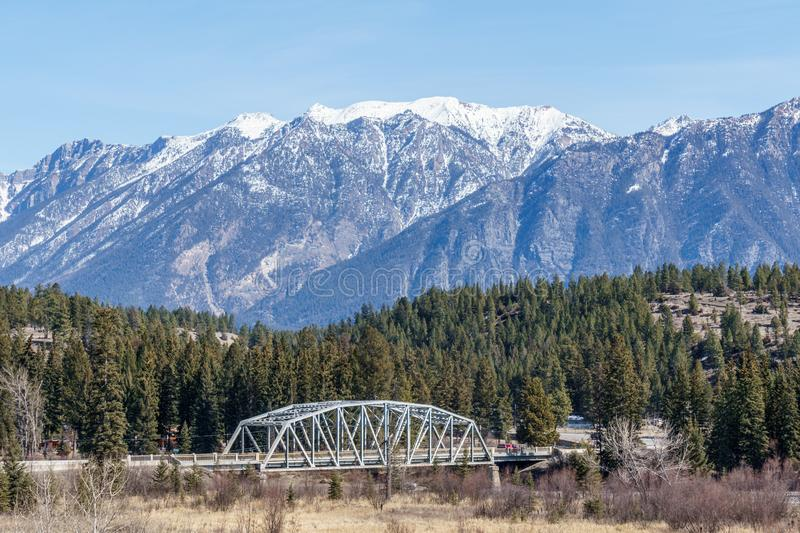 Metal bridge over a river with mountain in snow in the background Regional District of East Kootenay Canada. Road, blue, sky, landscape, travel, nature, sunny royalty free stock image