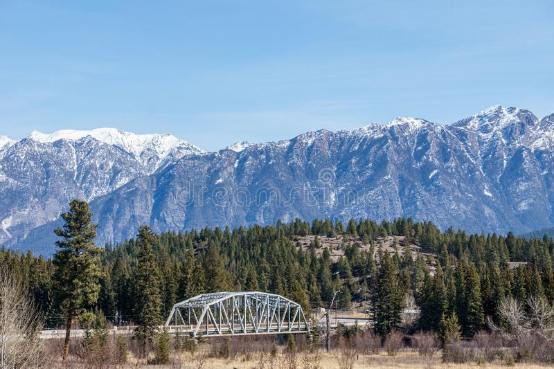 Metal bridge over a river with mountain in snow in the background Regional District of East Kootenay Canada. Road, blue, sky, landscape, travel, nature, sunny royalty free stock photos