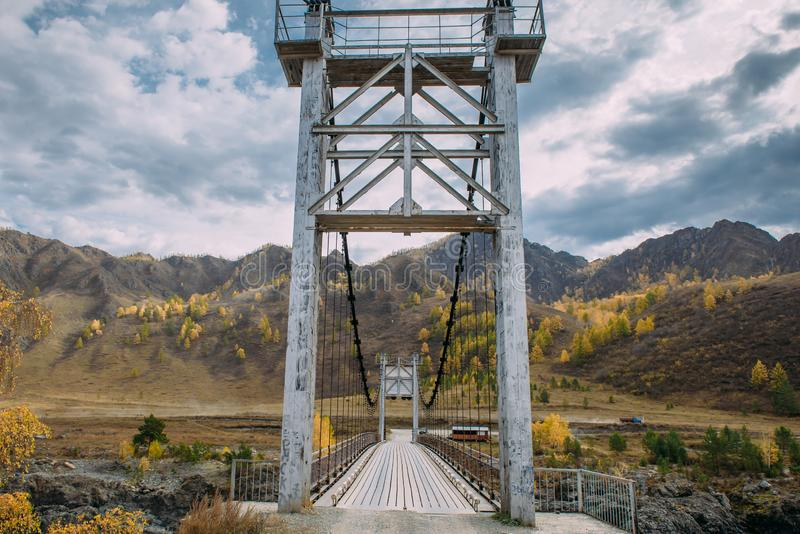 Metal bridge over river on mountains and storm clouds background. Combined pedestrian and road bridge over the river royalty free stock images