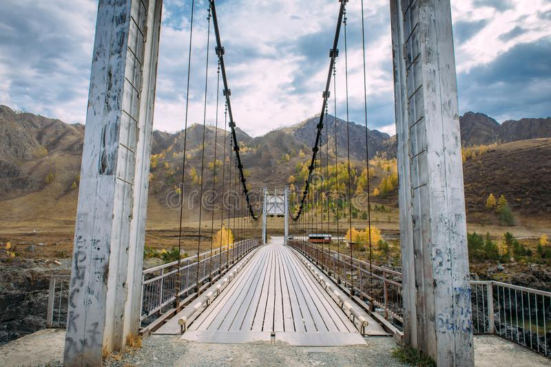 Metal bridge over river on mountains and storm clouds background. Combined pedestrian and road bridge over the river stock image