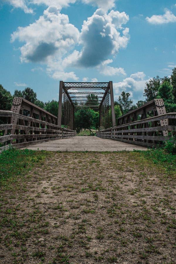 Metal Bridge Over River Under Blue Cloudy Skies. Metal footbridge with wooden walkway over a river under blue skies with puffy white clouds, old, sky stock images