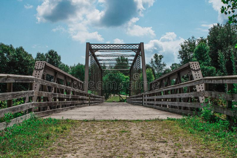 Metal Bridge Over River Under Blue Cloudy Skies. Metal footbridge with wooden walkway over a river under blue skies with puffy white clouds, old, sky royalty free stock image