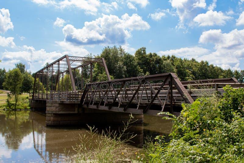 Metal Bridge Over River Under Blue Cloudy Skies. Metal footbridge with wooden walkway over a river under blue skies with puffy white clouds, old, sky stock photography