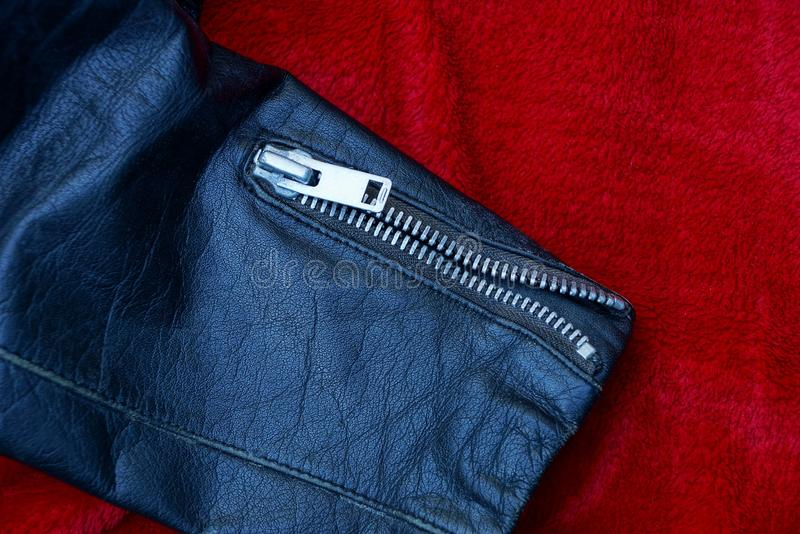 Metal buckle on a black leather sleeve jacket on red cloth stock photos