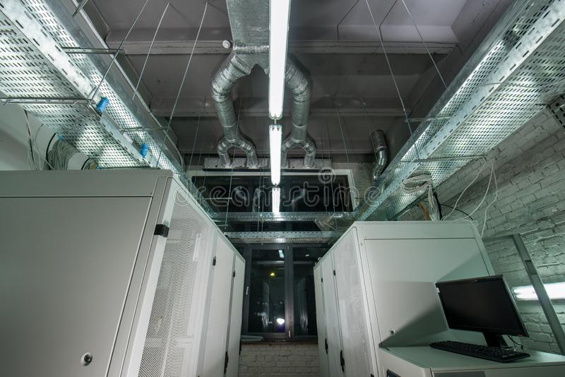 Metal cabinets with computers in the server room. The room is installed industrial exhaust air for ventilation stock photos