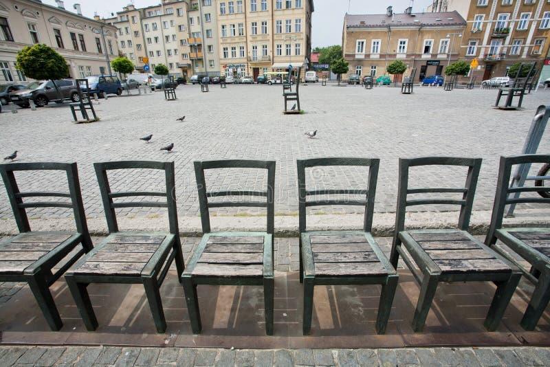 Metal cadeiras na rua cobbled na instalação da arte da cidade foto de stock