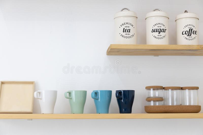 Metal can of coffee or tea and glass cup on wooden shelf with white wall. Background stock photos