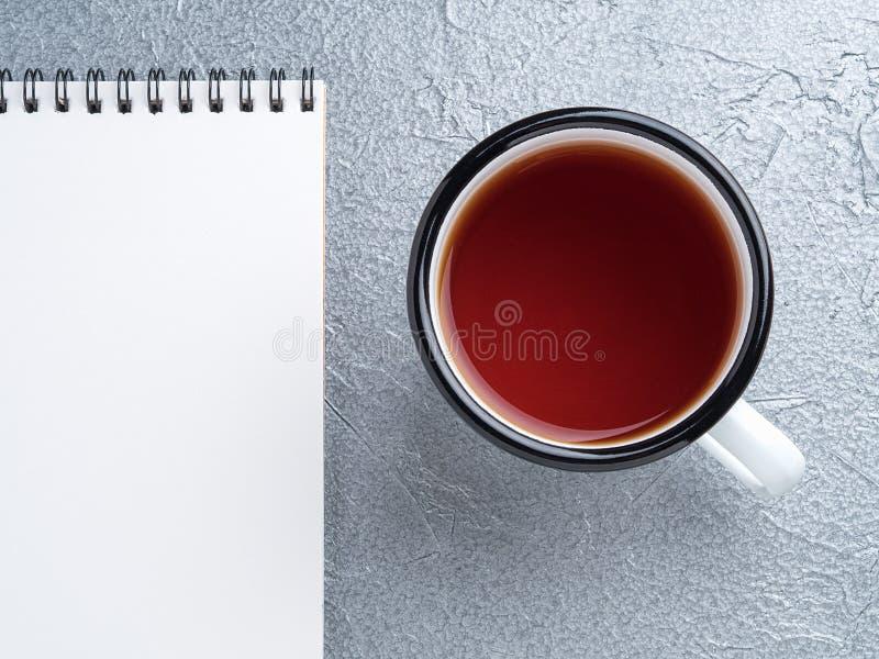 Metal a caneca com chá, esvazie uma folha vazia do bloco de notas na espiral fotografia de stock
