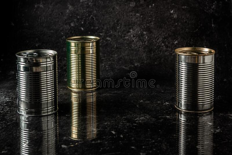 Metal cans on a black stone background on a reflective surface.  royalty free stock photo