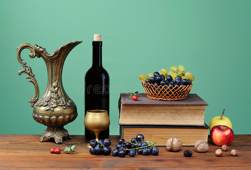 Metal carafe with fruits and book. On the table royalty free stock image