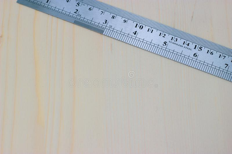 Metal carpentry ruler on a light wooden background stock photo