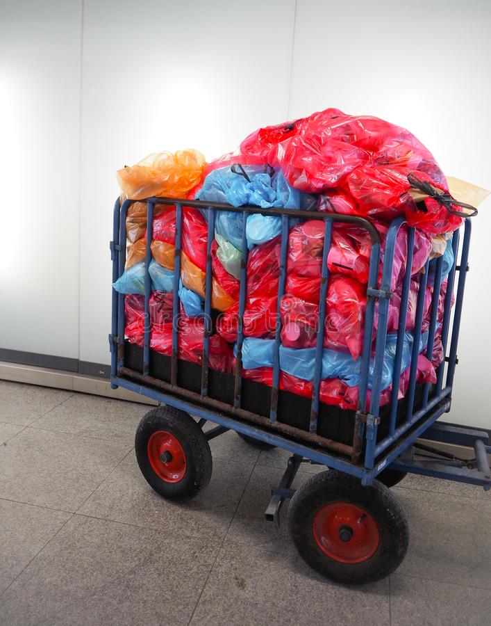 Metal cart for waste collection with a large pile of colorful plastic bags filled with sorted waste royalty free stock images