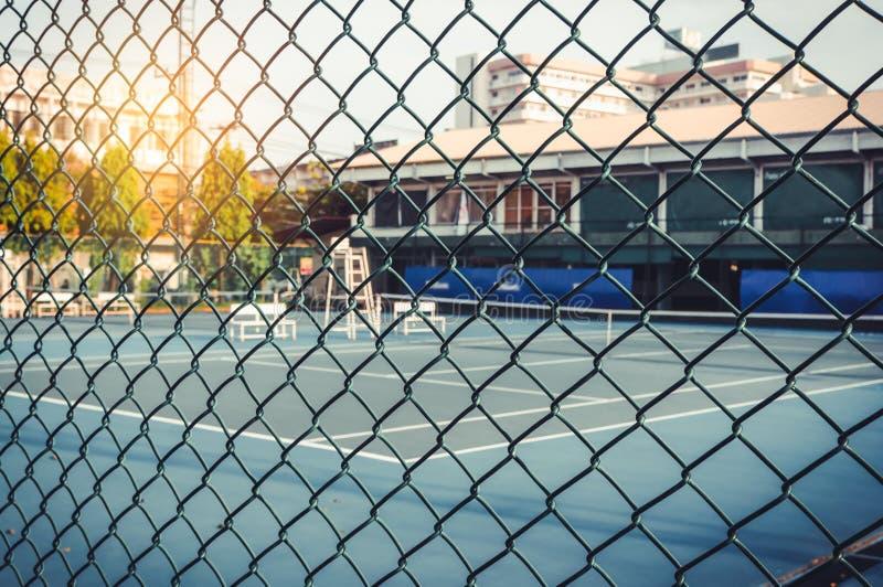 Metal a cerca de fio da malha com campo de tênis em obscuro para o fundo fotos de stock