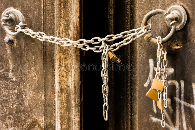 Metal chain closes an old door of an abandoned house. In an Italian village stock photo
