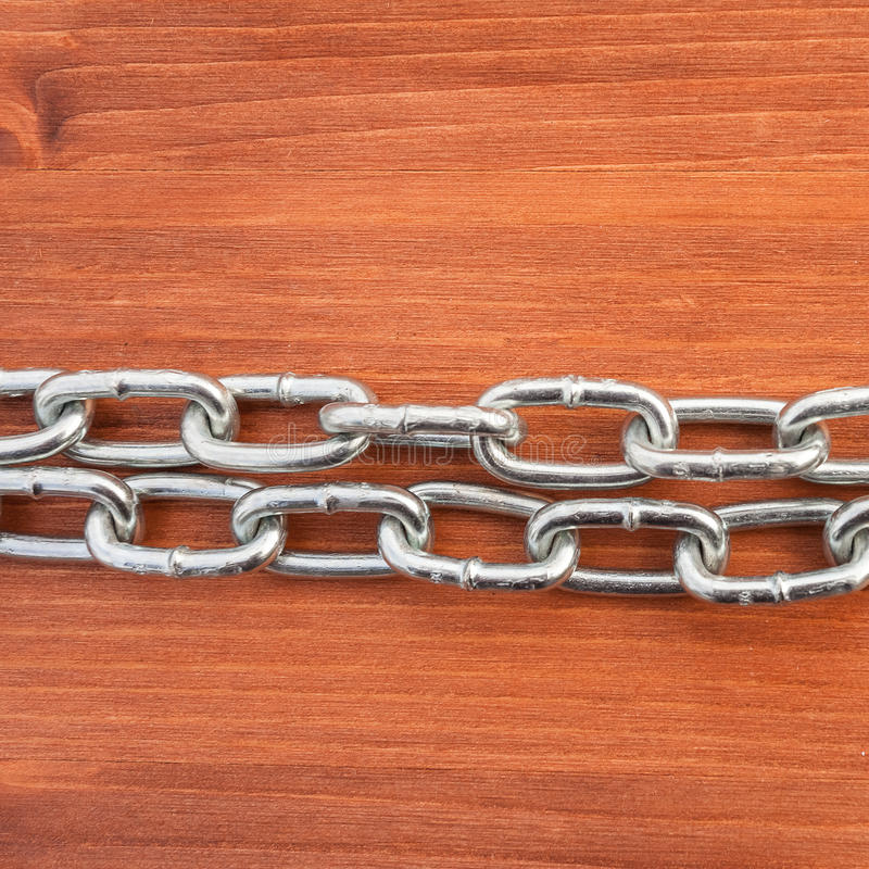 Metal chain links and lock. On wooden background stock photo