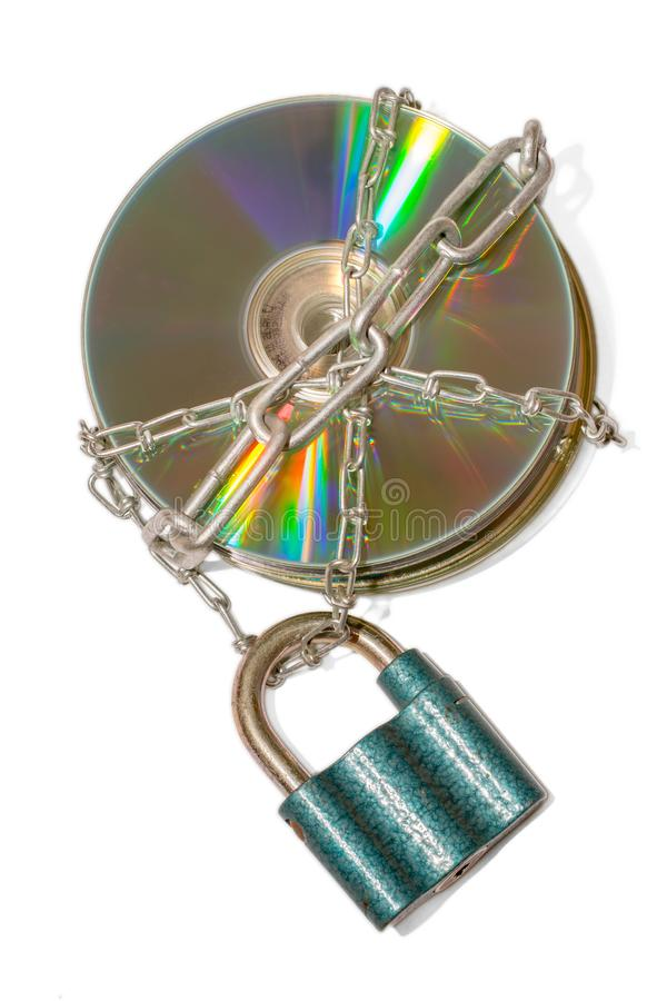 Metal chains encased in CDs as a symbol of data security. A stack of CDs as a cut-out against a white background with an iron chain and lock locked royalty free stock photography