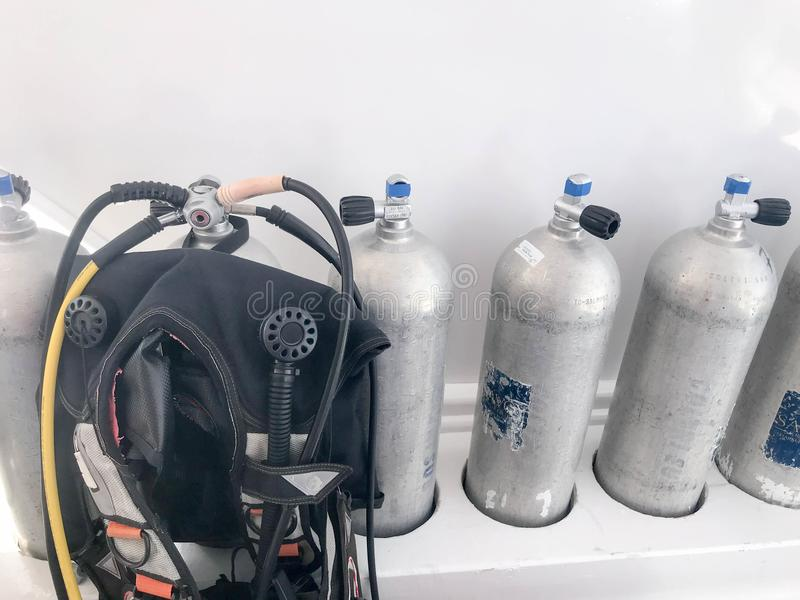 Metal chrome aluminum gas cylinders for breathing underwater, diving with valves, reducers and a black suit for diving with hoses royalty free stock photo