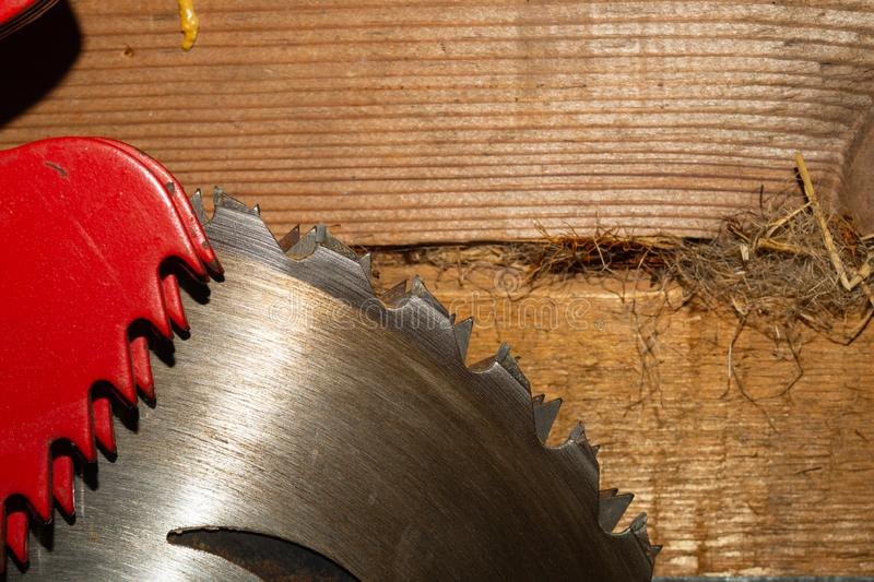 Metal circular saw blade on a wooden background. top view. working tool. carpentry instrument. Metal circular saw blade on a wooden background. top view. work stock image