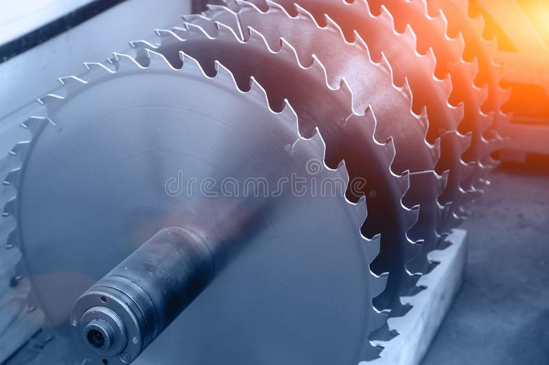 Metal circular saw blades for wood work as abstract industrial equipment tool background in blue color. Toned royalty free stock images