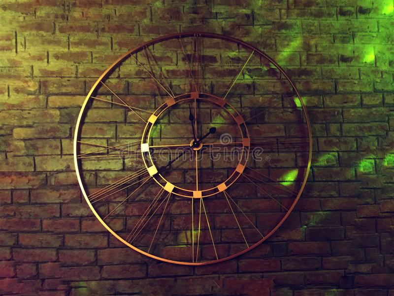 A metal clock on a brick wall. Geometrical clock highlighted perfectly by the neon light aura and fade brick wall stock photography