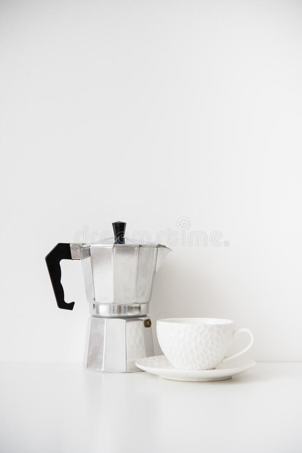 Metal coffee maker and white porcelain cup on table with blank wall royalty free stock image