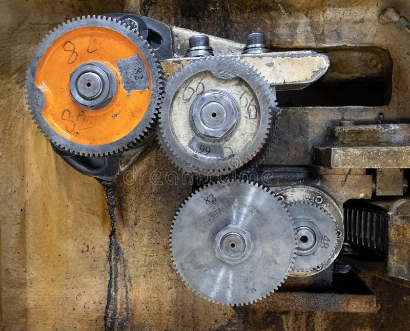 Metal cog wheels in gearing at gear box stock images