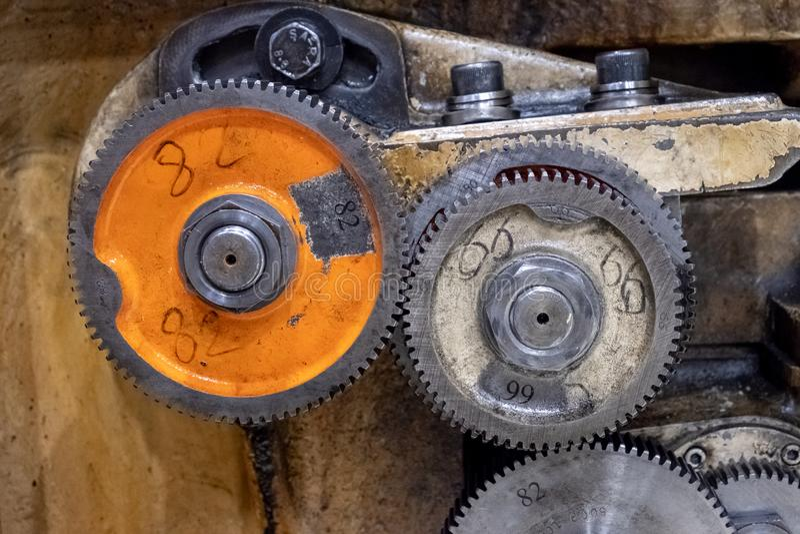 Metal cog wheels in gearing at gear box royalty free stock image