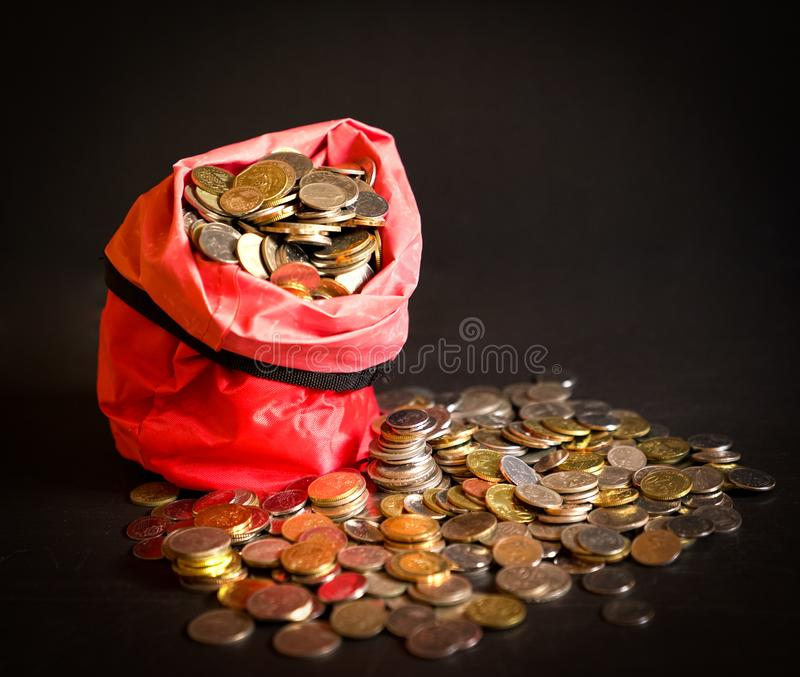 Metal coins in a red bag. Spilled over to the table. Dark background. Money or savings concept stock photos