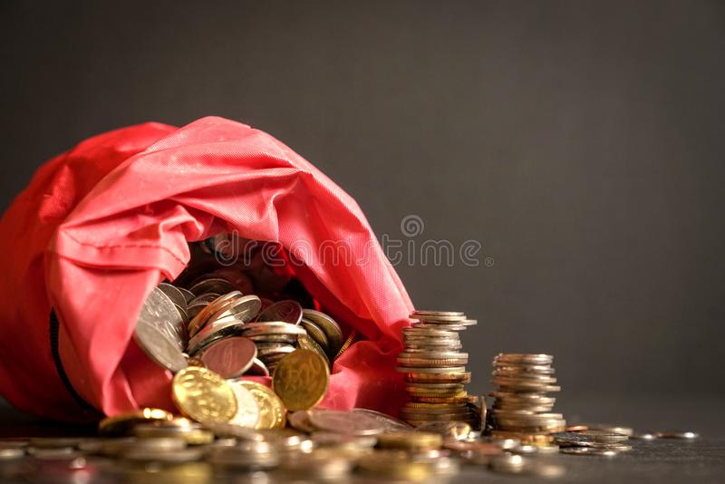 Metal coins in a red bag. Spilled over to the table. Dark background. Money or savings concept royalty free stock images