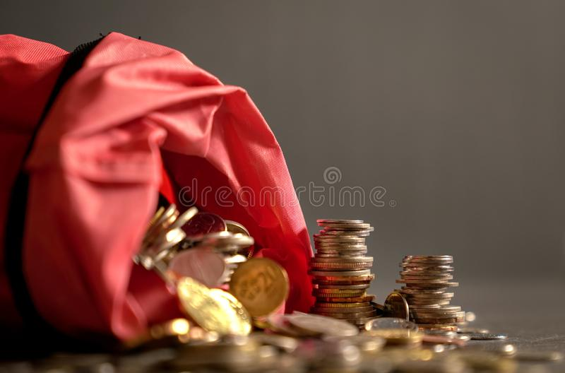 Metal coins in a red bag. Spilled over to the table. Dark background. Money or savings concept royalty free stock photography