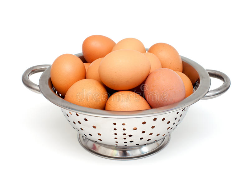 Metal colanger with eggs. Over white royalty free stock image