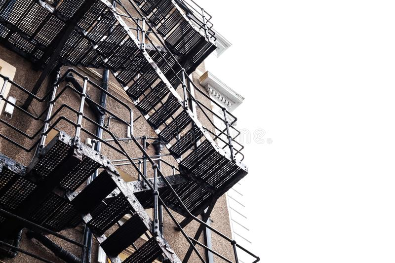 Metal construction on the building. Fire stairs on the old building. Frog perspective on the large old building with metal stairs. Metal construction on the stock photo
