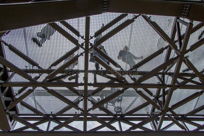 Metal construction. View from the bottom up with the people silhouettes.Background of a gray sky. Steel construction view from below royalty free stock photo