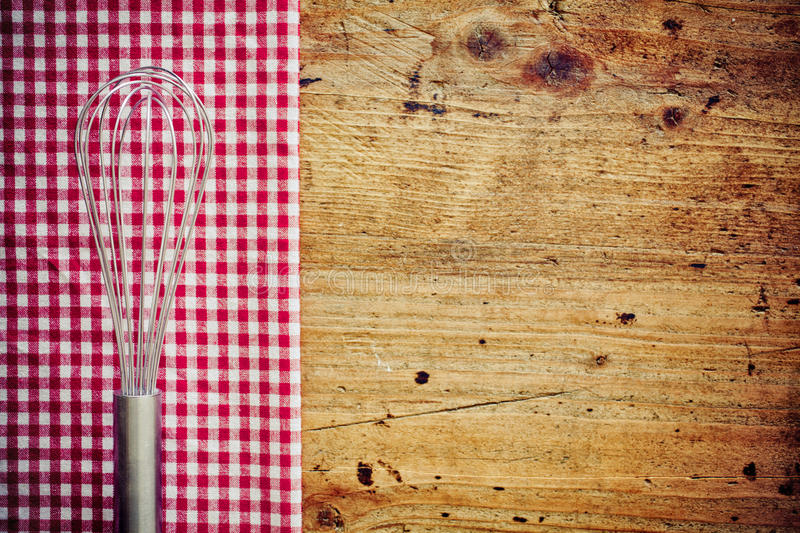 Metal cooking whisk. Or balloon whisk, lying on a fresh red and white checkered napkin on a wooden countertop in a rustic kitchen with copyspace stock images