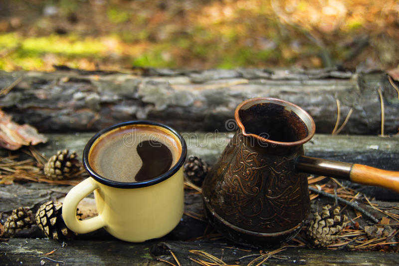 Metal cup with hot coffee and cezve on the wooden background with the coins, needles and bark of tree. royalty free stock images
