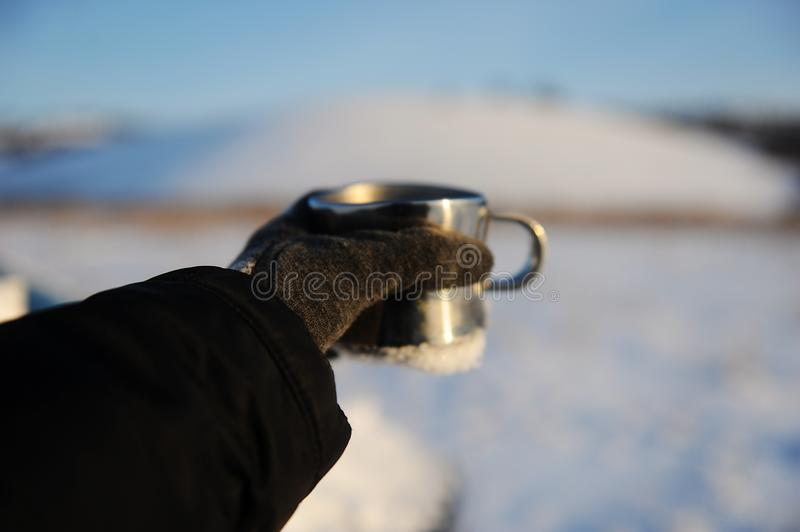 Metal cup in an outstretched hand on the background of a winter Russian snow landscape. Clear blue sky royalty free stock photo