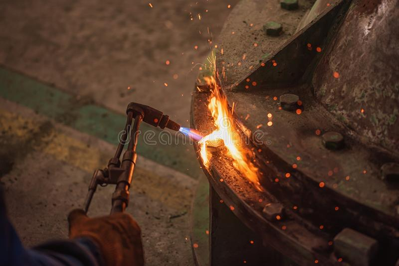 Metal cutting with acetylene and oxygen gas torch. Soft focus due to high ISO and shallow Depth Of Field. Metal cutting with acetylene and oxygen gas torch stock photos