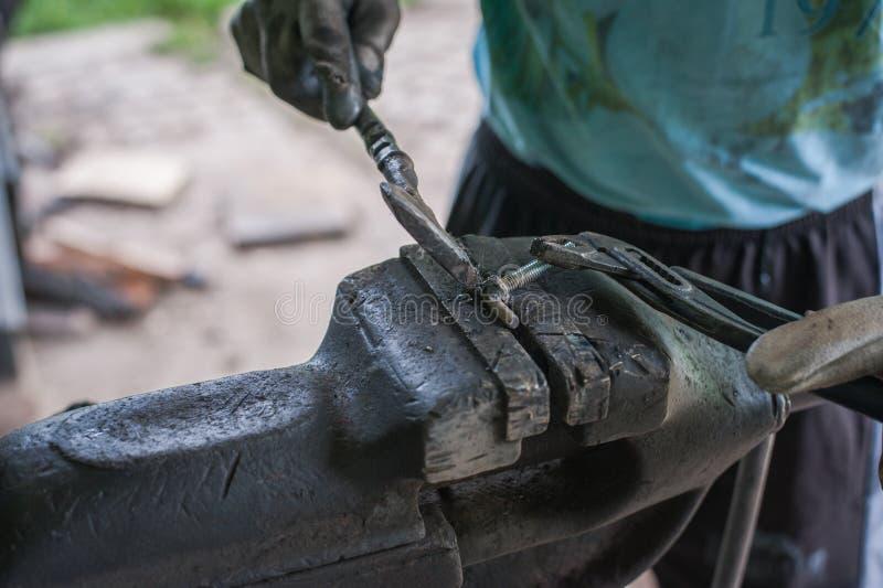 Metal de limpieza con un martillo después de soldar con autógena foto de archivo libre de regalías