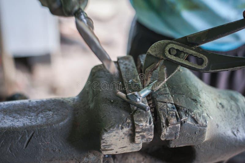 Metal de limpieza con un martillo después de soldar con autógena fotos de archivo